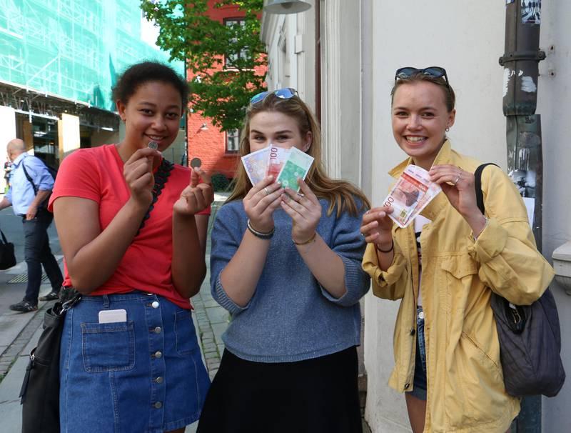 Bildet viser tre jenter. Jentene er 16 år gamle. De bruker kontanter når de handler.