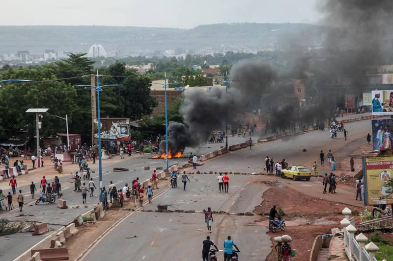 Bildet er fra forrige fredag. Da brente demonstranter blant annet bildekk i gatene i Bamako. Det er hovedstaden i Mali. Det er svart røyk på bildet, og mye folk i gatene. Det er bare en bil, og den står på en sidevei.