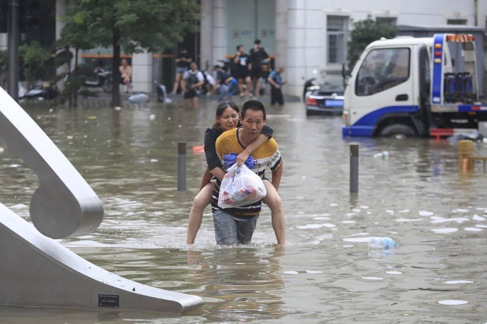 En mann bærer en kvinne gjennom en oversvømt gate i byen Zhengzhou i Kina 21. juli. Over 300 mennesker mistet livet i flommen i Henan-provinsen. Foto: Chinatopix / AP / NTB
