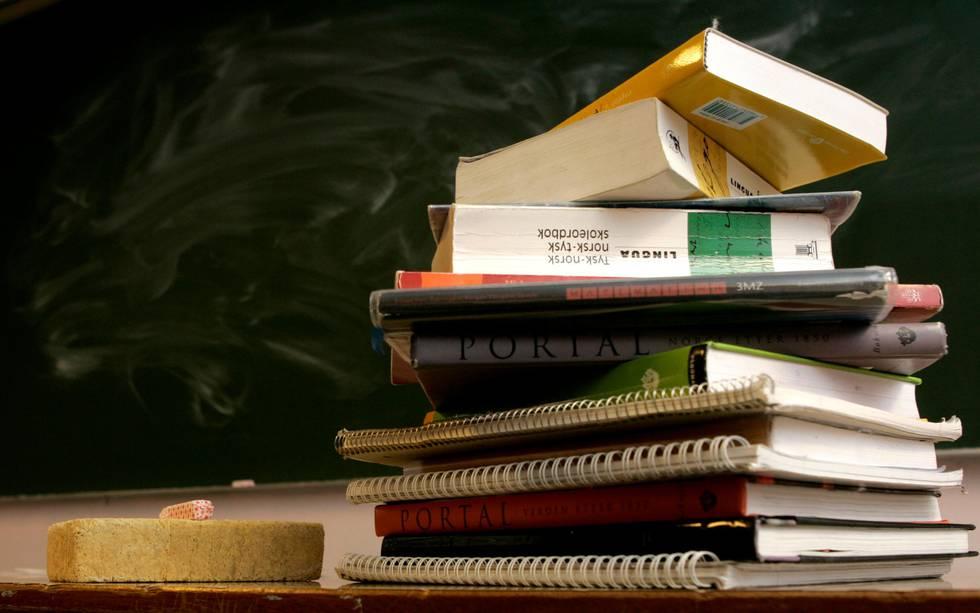 Bildet er av en stabel med bøker. I bakgrunnen er det en skoletavle.