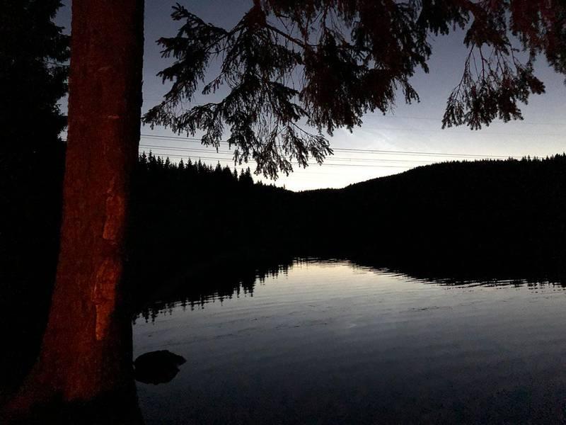 Bildet viser et vann med skog i bakgrunnen. Solen begynner så vidt å stå opp bak horisonten. Fra teltplassen kan du nyte stjernehimmel og soloppgang. Hvis du er heldig med været.
