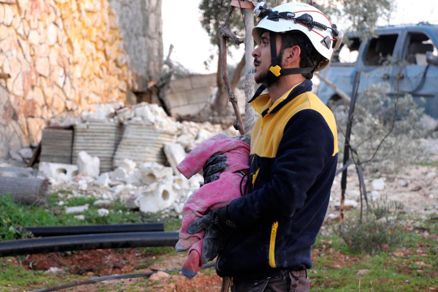 This photo provided by the Syrian Civil Defense White Helmets, which has been authenticated based on its contents and other AP reporting, a Syrian White Helmet civil defense worker carries a child victim after Russian airstrikes hit Maaret Musreen village, in Idlib province, Syria, Thursday, March 5, 2020. An airstrike on a rebel-held village in northwestern Syria early Thursday. (Syrian Civil Defense White Helmets via AP)
