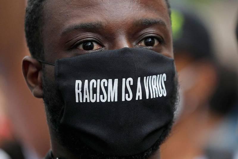Bildet viser en demonstrant i London med munnbind med slagord på.