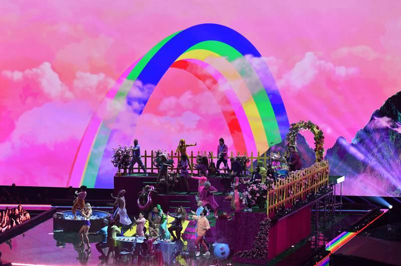 Bildet viser Taylor Swift og mange andre på scenen. Det er en regnbue i bakgrunnen.