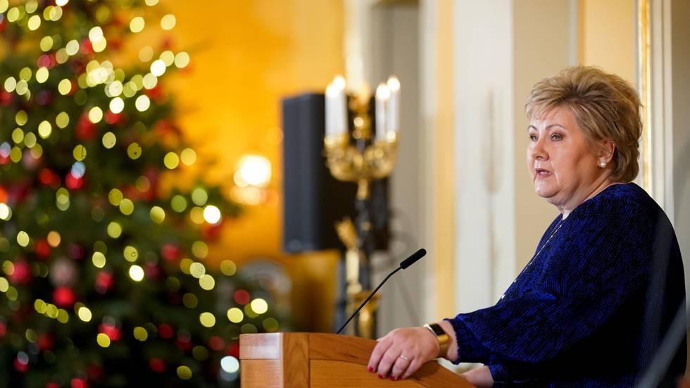 Bildet viser statsminister Erna Solberg. Hun står ved et pyntet juletre.