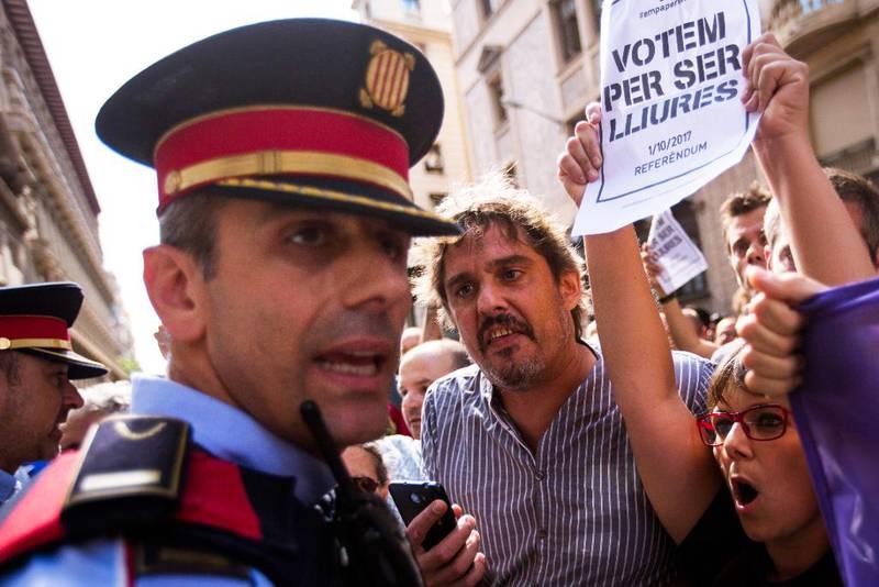 Bildet viser folk som roper til en spansk politimann i Catalonia.