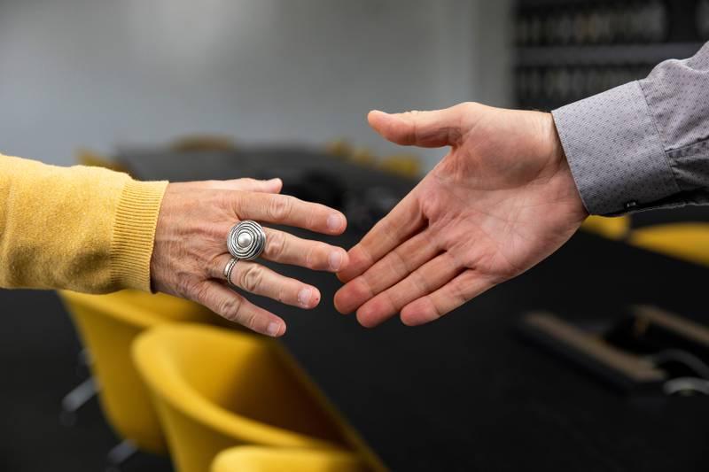 Bildet viser to hender som er i ferd med å møtes i et håndtrykk.