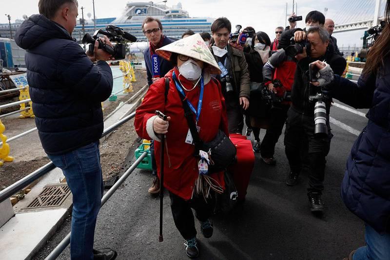 Bildet viser passasjerer på vei ut fra cruiseskipet Diamond Princess. Omtrent 500 passasjerer får slippe ut fra skipet. Det har ligget til kai i Japan siden starten av februar.