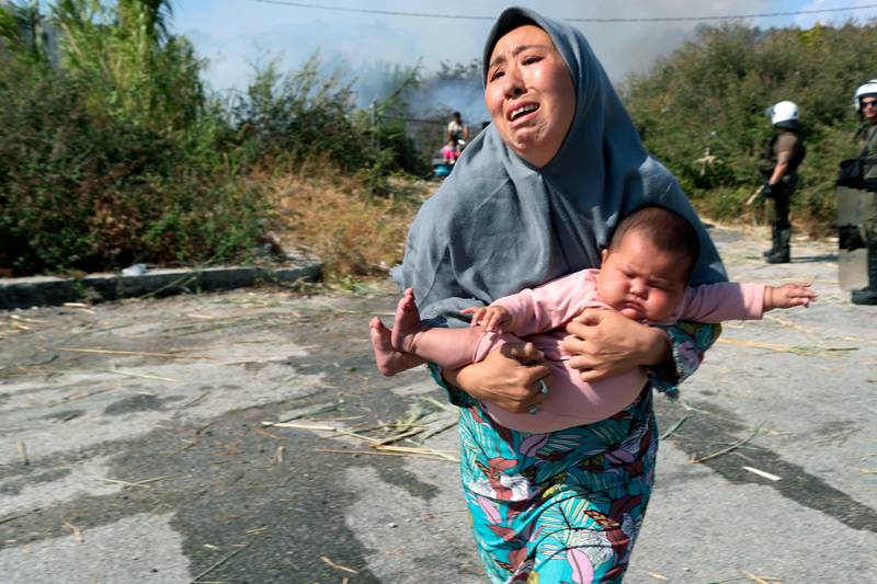 A migrant holds her baby as she runs to avoid a small fire in a field near Mytilene town, on the northeastern island of Lesbos, Greece, Saturday, Sept. 12, 2020. Thousands of asylum-seekers spent a fourth night sleeping in the open on the Greek island of Lesbos, after successive fires destroyed the notoriously overcrowded Moria camp during a coronavirus lockdown. (AP Photo/Petros Giannakouris)