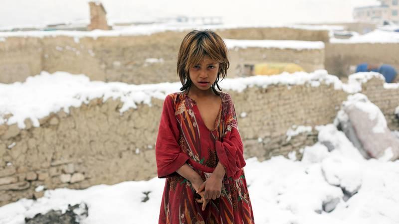 Bildet viser ei ung jente i Afghanistan. Det har snødd der hun bor.