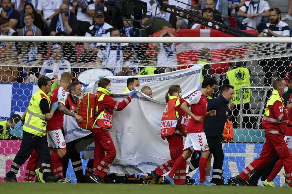 Bildet viser Christian Eriksen som blir båret ut fra fotballbanen.