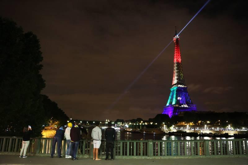 Bildet viser Eiffeltårnet i Paris i Frankrike lyst opp av regnbuens farger.