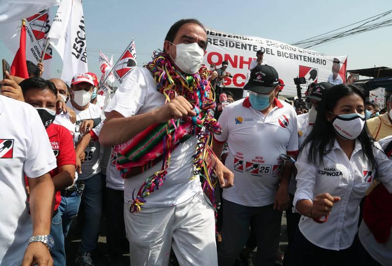 Yonhy Lescano danser på et valgmøte i Lima i Peru. Han har på hvite klær, munnbind og fargerike tøystykker rundt halsen.
