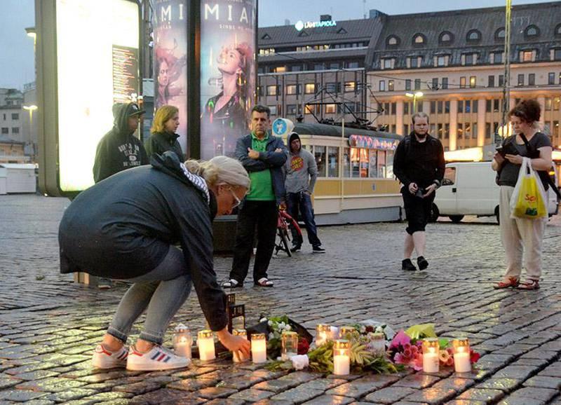 Bildet viser folk som tenner lys på plassen der ti mennesker ble knivstukket fredag.