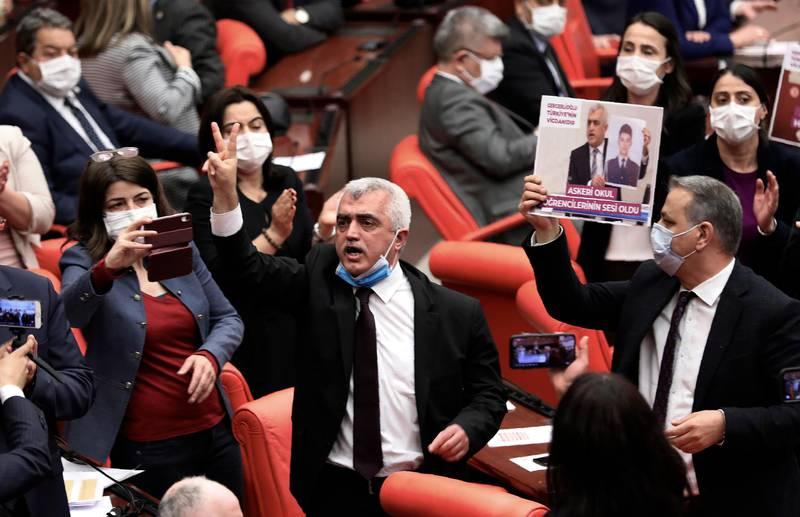 Bildet er av Ömer Gergerlioglu. Han står blant en gruppe folk i nasjonal-forsamlingen. Han har munnbind på haka. De tar bilder og filmer måten han reagerer på at han har mista sin plass i nasjonal-forsamlingen.