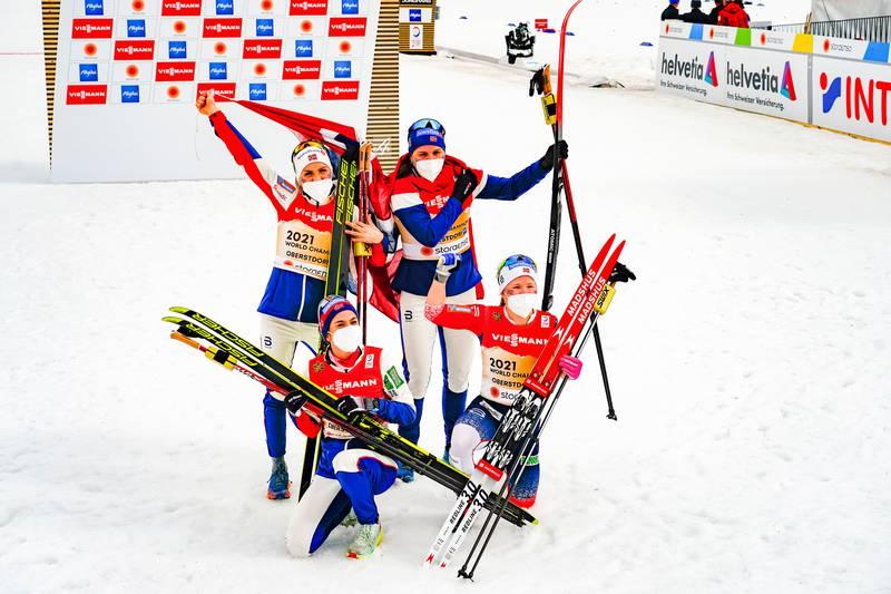Bildet er av de fire damene som deltok i stafett for Norge. De vant gull. De står i målområdet og jubler.