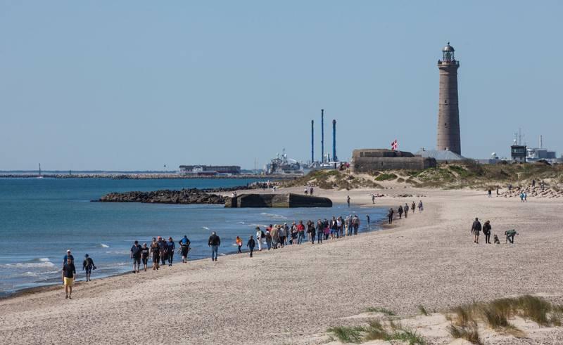 Bildet er av en strand i Skagen i Danmark. I det fjerne er et fyrtårn og en havn. Det er folk som går langs stranden.