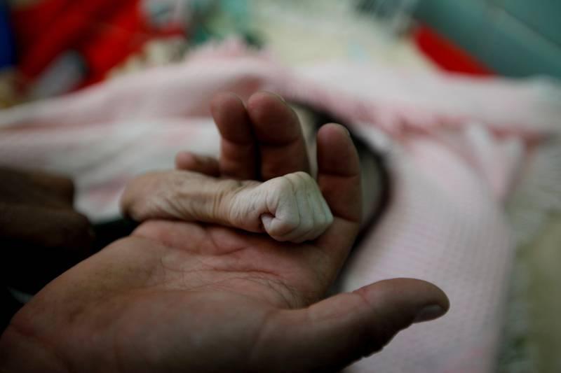 Bildet viser to hender. En far holder datteren sin hånd.