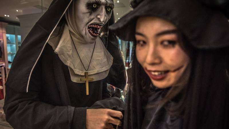 Bildet viser to personer i Kina med maske og sminke.