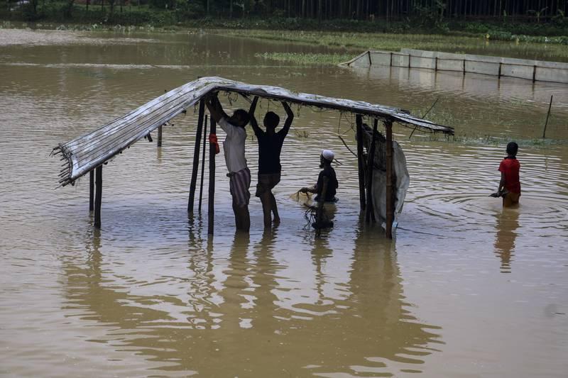 Bildet er av flyktninger som reparerer en hytte som er ødelagt av regn. De står i dypt vann.