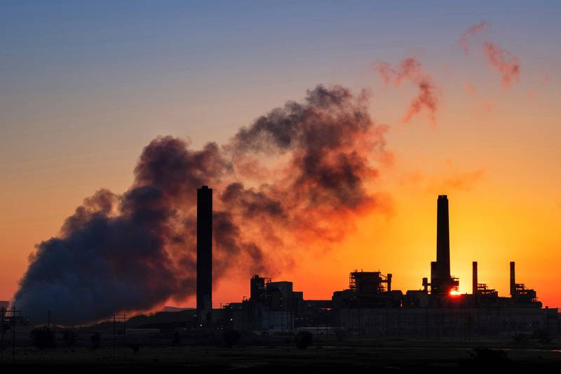 Bildet er av pipene fra et kullkraftverk mot solnedgangen. Det er mye røyk i bildet.