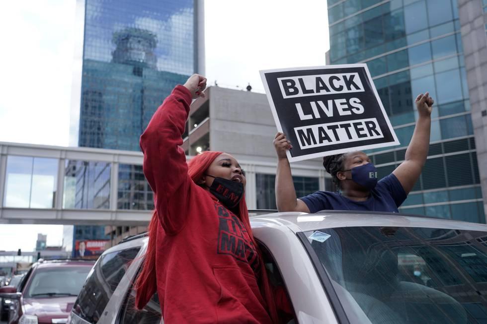 Bildet viser amerikanere med et skilt der det står Black Lives Matter.