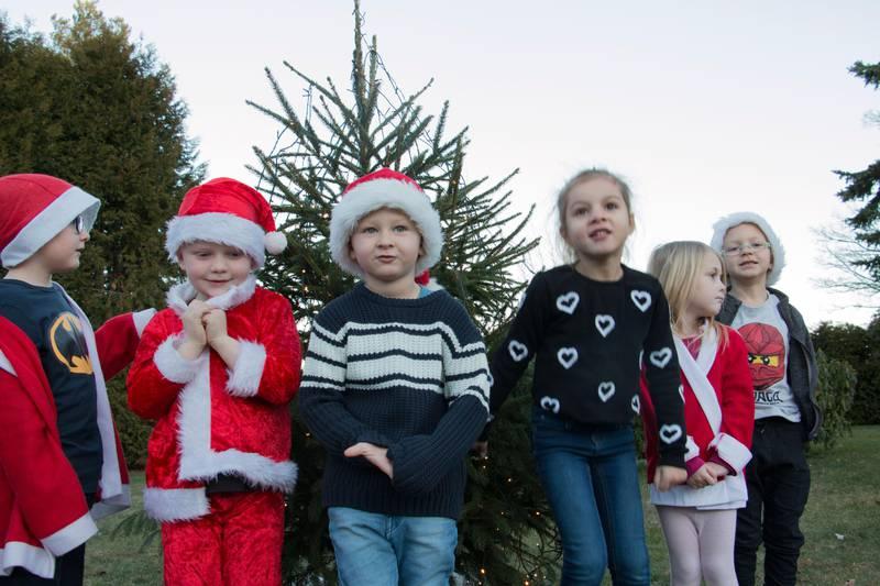 Bildet viser seks barn som står ute foran et juletre med lys i.
