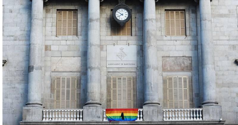 Bildet viser rådhuset i Barcelona i Spania pyntet med regnbueflagget.