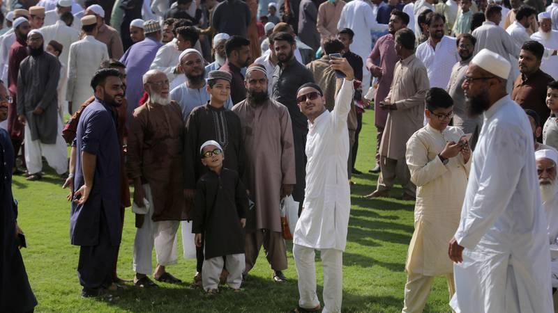 Bildet viser en pakistansk mann som tar selfie sammen med familien. Pakistanere og andre feirer id.