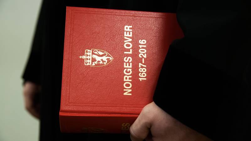 Bildet viser noen som holder boka Norges lover.