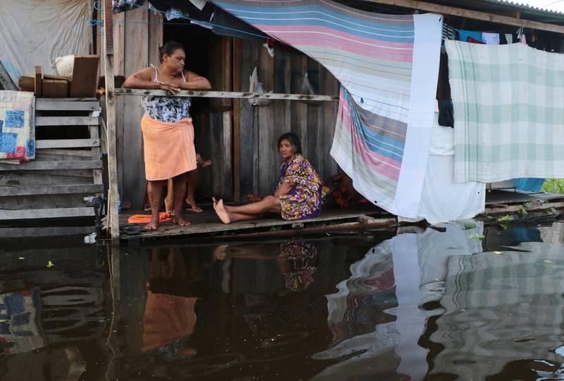 Bildet er av to kvinner på en trapp til huset sitt i Manaus. Vannet er bare noen få centimeter nedenfor.