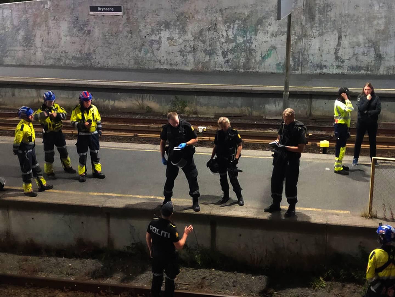 Flere politi står på perongen til t-banestasjonen. Mens noen er nede å leter på selve skinnene.