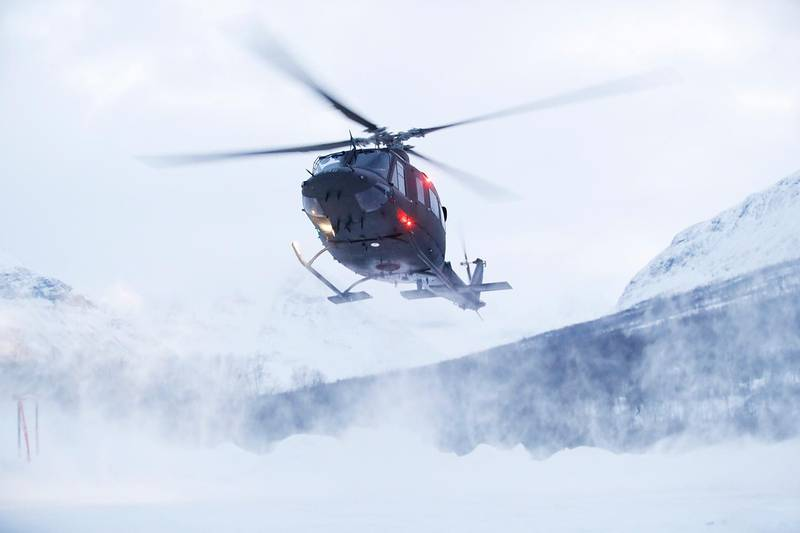 Bildet viser et helikopter fra Forsvaret. Det flyr over Tamokdalen i Troms.