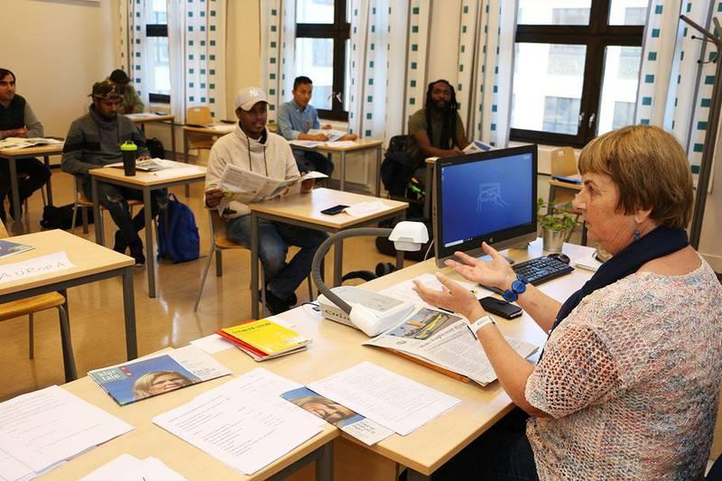 Bildet viser Bodil Johanne Knutsen bak kateteret i klasserommet på Rosenhof i Oslo. Foran henne sitter flere elever. Hun har undervist innvandrere i norsk i mange år. Hun bruker Klar Tale i undervisningen.