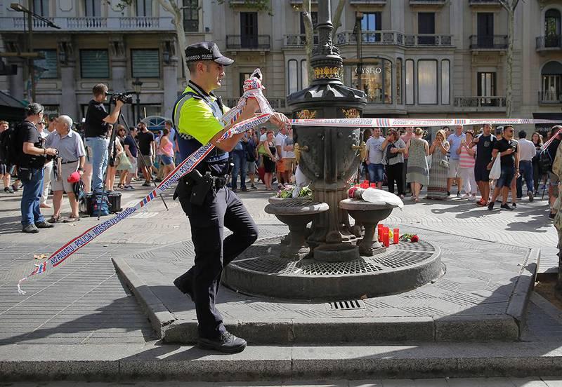 Bildet viser en politimann som fjerner et sperrebånd.