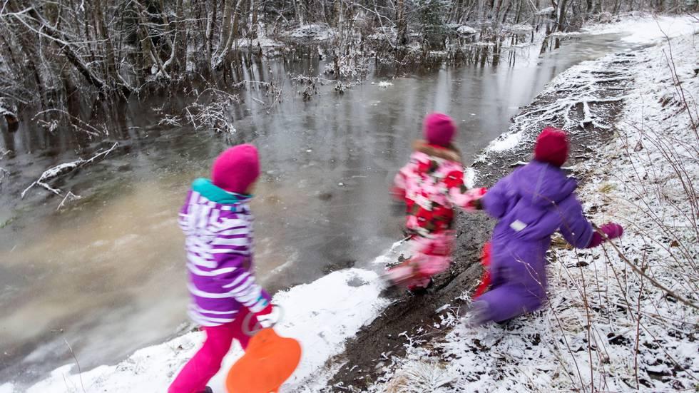 Bildet viser barn som løper langs et vann på vinteren.