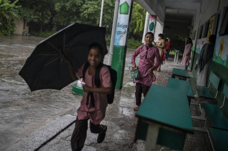 Bildet er av elever som kommer tilbake på skolen i en forstad i byen New Delhi i India. Den fremste har en paraply og smiler. Det er regnvær, men de går under et tak.