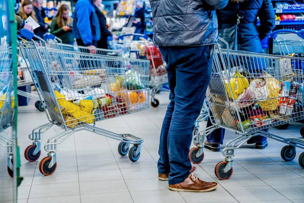 Bildet er av handlevogner og beina på folk som står i kø på matbutikken.