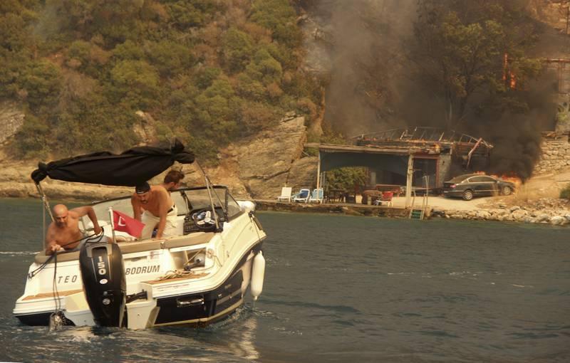 Sommerparadiset langs kysten ved Bodrum i Tyrkia er blitt et branninferno der folk desperat flyktet fra flammene i feriebåter søndag. Foto: IHA via AP / NTB