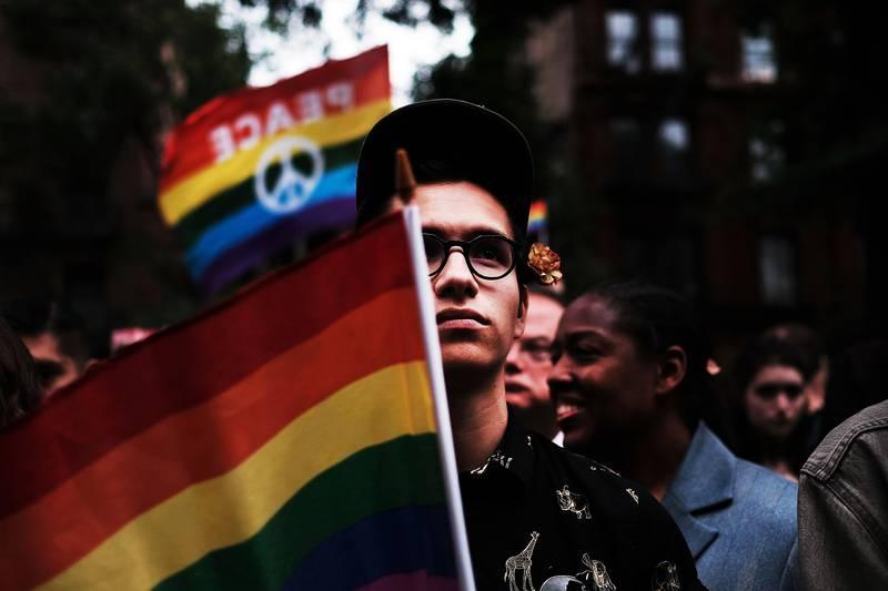 Bildet viser en mann som holder regnbueflagget.