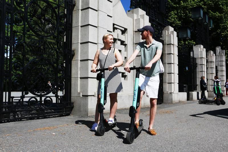 Bildet viser Nathalie Greiner og Henrik Haugen som viser fram elektriske sparkesykler.