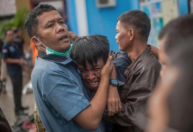 Bildet viser en ung mann som gråter. Han får trøst fra en hjelpearbeider.