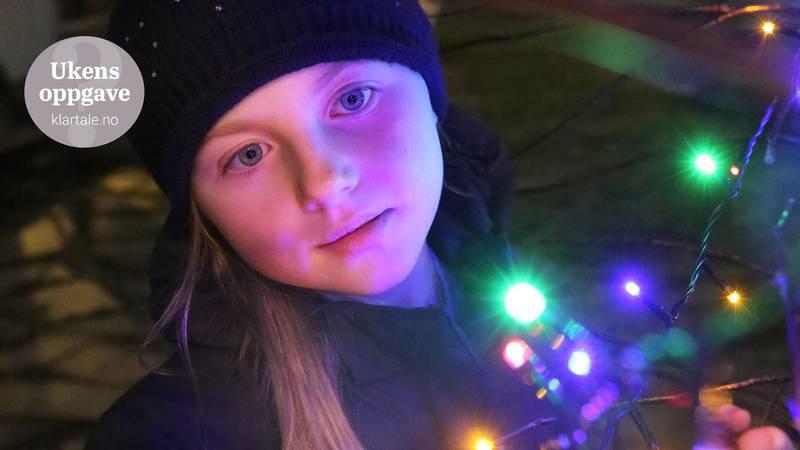 Bildet viser ei jente som ser på fargerike julelys.
