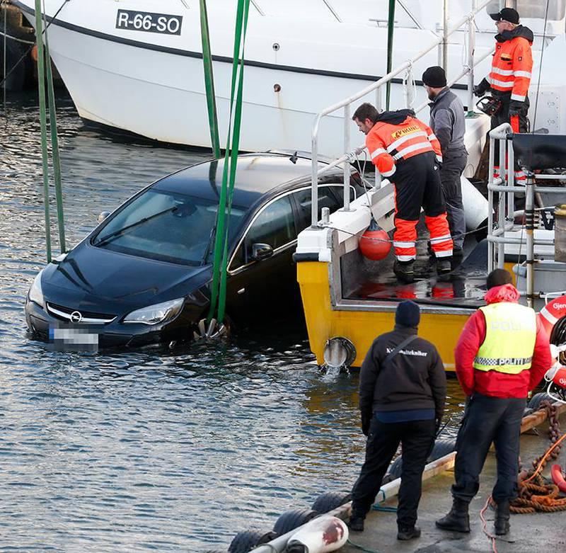 Bildet viser en sort bli som blir hevet opp av vannet onsdag. Den tilhører trolig en mann som ble funnet død mandag. Politiet tror tre menn ville stjele bilen. De er siktet for drap.