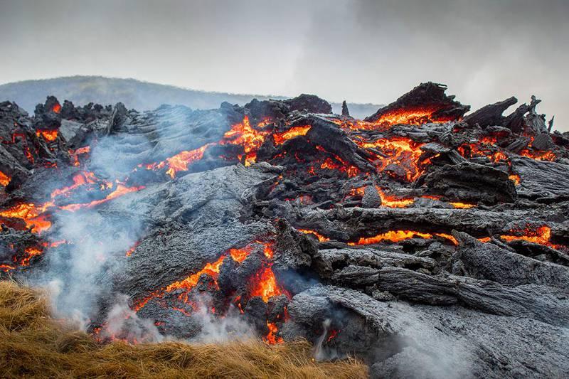 Bildet viser rødglødende lava som strømmer ut av vulkanen Fagradalsfjall på Island.