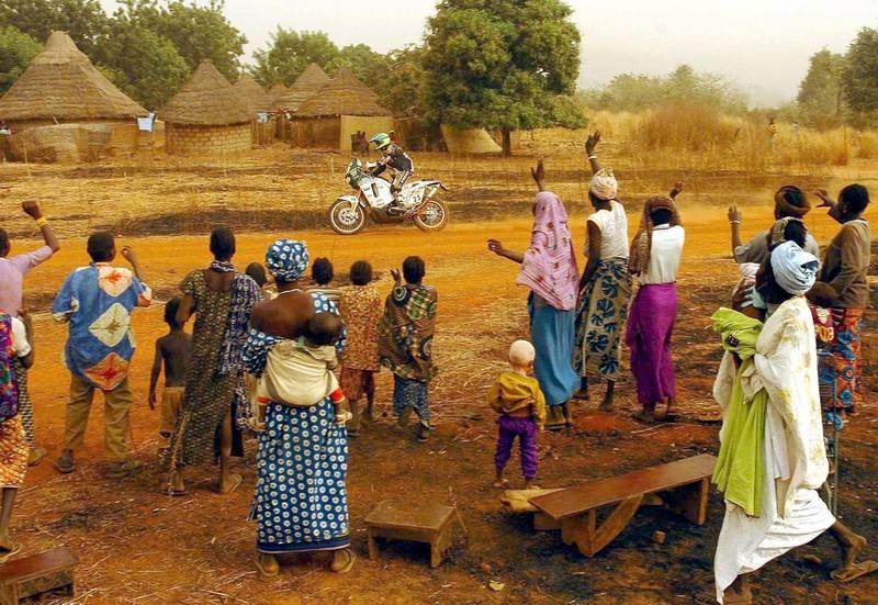 Bildet viser folk i Mali som vinker til en motorsyklist.