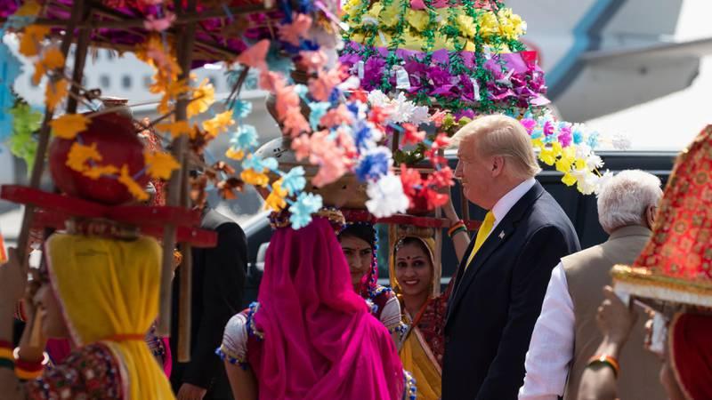 Bildet viser indiske damer kledd i sterke farger. Donald Trump er på besøk.