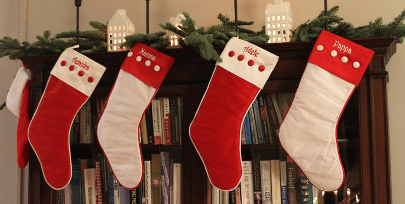 Bildet viser jule-strømper som henger fra en hylle.