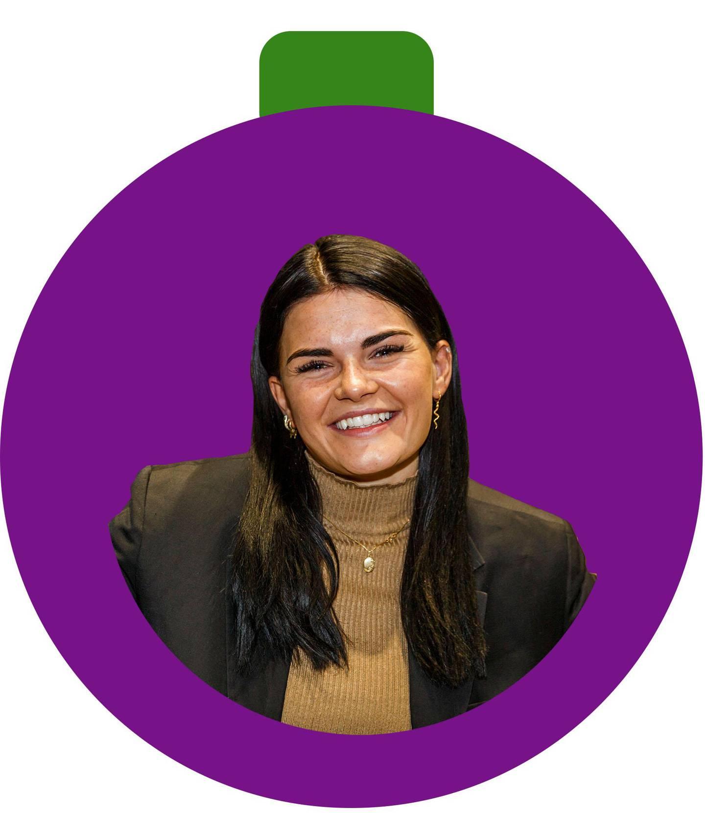 Bildet er av en lilla julekule. Det er en mørkhåret artist i kula. Hun har vunnet Melodi Grand Prix i Norge.