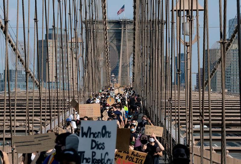 Bildet viser demonstranter som marsjerte fredelig over Brooklyn Bridge i New York lørdag.